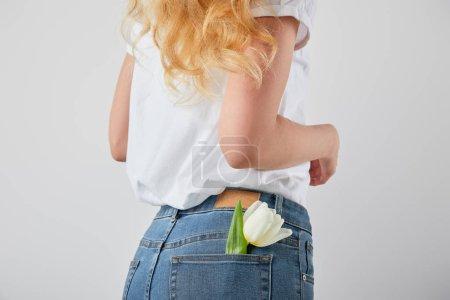 Photo pour Vue recadrée de fille avec fleur de tulipe dans la poche de jeans isolé sur fond gris - image libre de droit