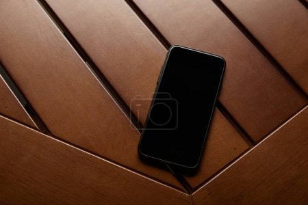 Photo pour Vue du haut du smartphone avec écran blanc sur table en bois - image libre de droit