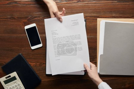 Photo for Top view of businesspeople holding contract at workplace with copy space - Royalty Free Image