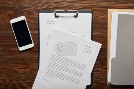 Photo for Top view of documets on clipboard, smartphone and folder on table - Royalty Free Image