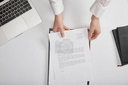 Photo pour Recadrée vue du greffier mettant document sur presse-papiers au lieu de travail - image libre de droit