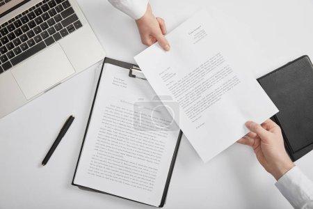 Photo pour Vue de dessus de détenir le document à l'espace de travail des employés de bureau - image libre de droit