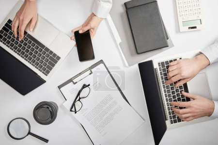 Photo pour Vue d'en haut des gens d'affaires tapant sur les ordinateurs portables et tenant smartphone - image libre de droit