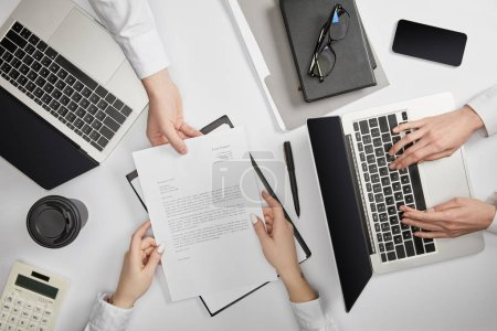 Photo for Top view of businesspeople typing on laptop and holding document - Royalty Free Image