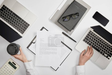 Photo for Cropped view of office worker holding paper cup and typing on laptop - Royalty Free Image