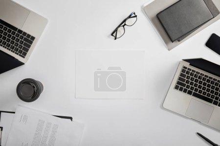 Photo pour Vue du haut du document sur presse-papiers, tasse en papier, ordinateurs portables, stylo, cahiers, dossier, lunettes et papier blanc - image libre de droit