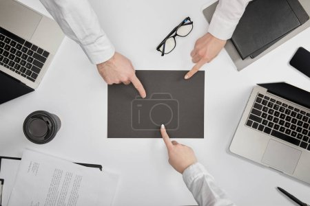 Photo for Top view of businesspeople pointing to blank grey paper at workplace - Royalty Free Image