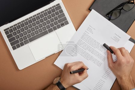 Photo pour Vue recadrée de l'homme d'affaires signant document avec stylo sur le lieu de travail - image libre de droit