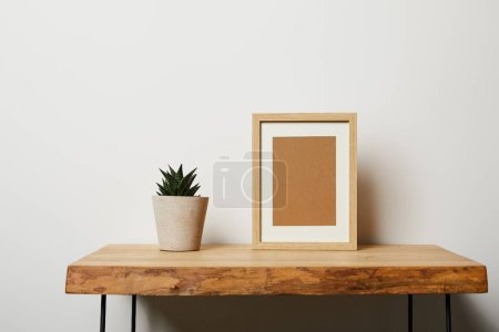 Photo for Green plant near frame on wooden table at home - Royalty Free Image