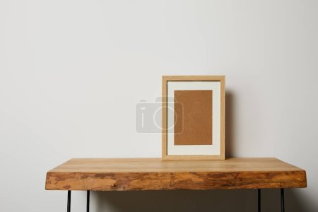 Photo for Blank square frame on wooden textured table at home - Royalty Free Image