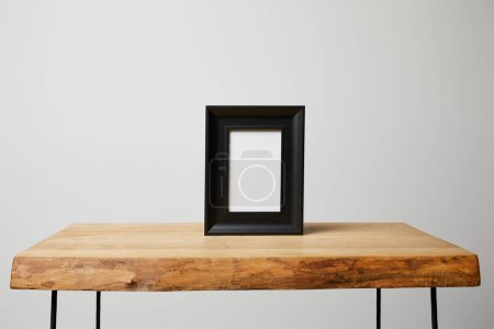 Photo pour Cadre carré noir sur une table en bois à la maison - image libre de droit