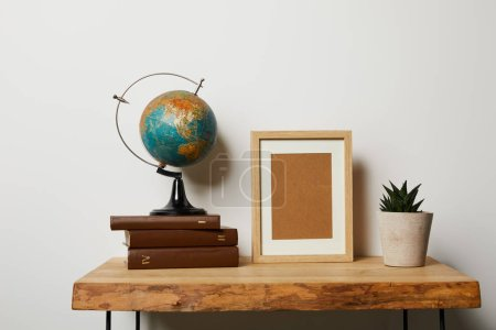 globe on books near frame and plant in pot on table