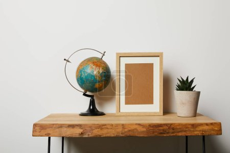 globe near frame and plant in pot on wooden table
