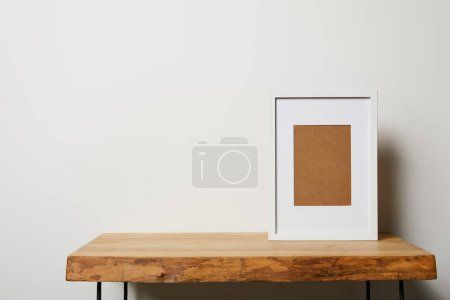 blank frame on wooden table on white background