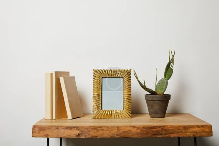 Photo for Books near golden frame and cactus in pot on wooden table - Royalty Free Image