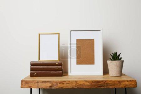 Foto de Libros cerca de cactus en maceta y marcos en madera mesa - Imagen libre de derechos