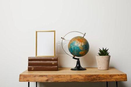 Foto de Marco en libros cerca globo y planta verde en maceta - Imagen libre de derechos