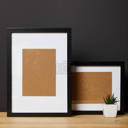 Photo for Black blank frames on wooden table near green plant in pot - Royalty Free Image