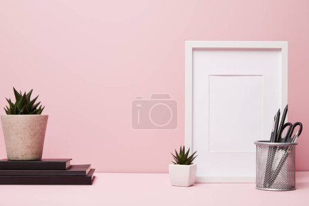 Photo for Blank frame near green plant, metallic holder with stationery and books - Royalty Free Image