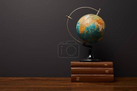 globe near books on wooden textured table