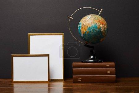 Foto de Globo en libros cerca de marcos en blanco sobre la mesa - Imagen libre de derechos