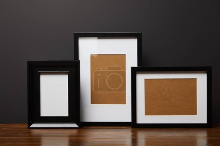 black blank square frames on wooden table
