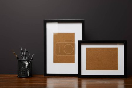 black square frames near metallic holder with stationery on wooden table