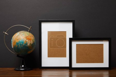 globe near blank black frames on wooden table