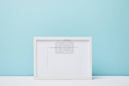 Photo for White square frame on white surface near blue wall - Royalty Free Image