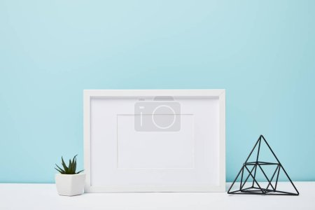 white square frame near green plant in pot on white surface