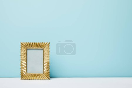Photo for Golden frame on white surface near blue wall - Royalty Free Image