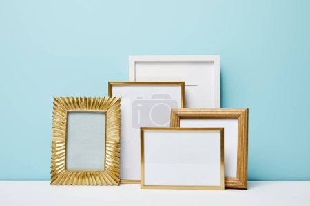 golden decorative square frames near blue wall