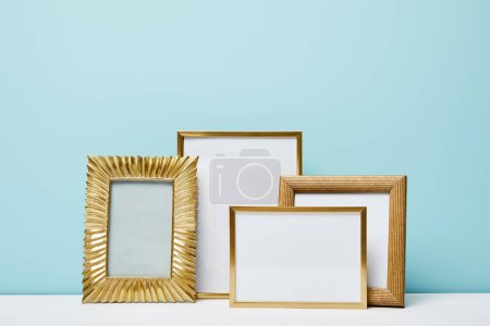 blank square decorative frames near blue wall