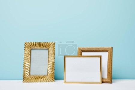blank decorative frames near blue wall
