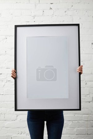 Photo for Woman covering face while holding blank black frame in hands - Royalty Free Image