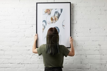 Photo for Back view of woman holding drawing in black square frame - Royalty Free Image