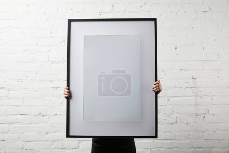 woman covering face while standing and holding blank black frame