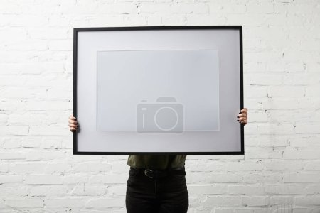 Photo for Woman covering face while standing and holding blank frame in hands - Royalty Free Image