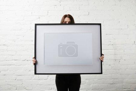 Photo pour Vue recadrée femme couvrant le visage tout en se tenant debout et tenant le cadre vide dans les mains - image libre de droit