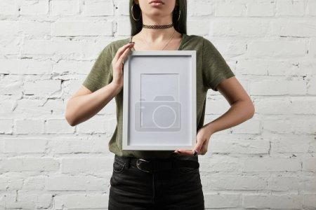 Photo pour Vue recadrée de femme debout et tenant blanc cadre blanc en mains - image libre de droit