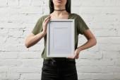 """Постер, картина, фотообои """"обрезанный вид женщины стоя и держа в руках пустой белый кадр"""""""