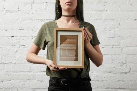 Photo pour Vue recadrée de femme debout et tenant le cadre carré blanc en mains - image libre de droit