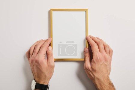 Photo pour Vue recadrée de l'homme maintenant cadre vide en mains sur fond blanc - image libre de droit