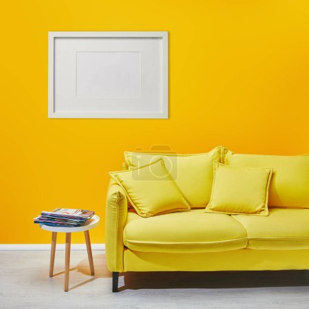 Photo for Coffee table standing near modern yellow sofa near white frame hanging on wall - Royalty Free Image