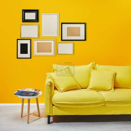 Photo for Coffee table standing near modern yellow sofa near decorative frames hanging on wall - Royalty Free Image