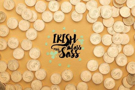 Foto de Vista superior de monedas de oro con signos de dólar y círculo de tréboles cerca de letras sobre fondo naranja - Imagen libre de derechos