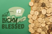 top view of golden coins near not lucky just blessed lettering on green background