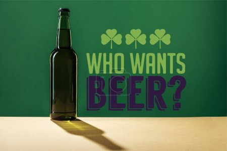 Photo pour Verre bouteille de bière près de qui veut lettrage bière sur fond vert - image libre de droit