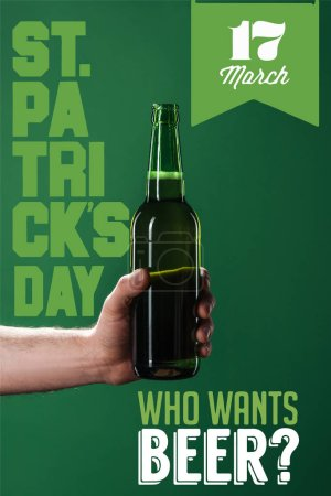 Photo for Cropped view of man holding beer bottle near who wants beer lettering on green background - Royalty Free Image
