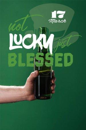 Photo pour Recadrée de l'homme tenant la bouteille de bière près de pas de chance juste béni sur fond vert - image libre de droit